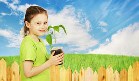 Little girl holds a pot with the seedling next to garden fence Stock Images
