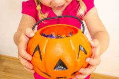 A little girl holds a pumpkin with candy in her hands and stretches it to get even more candies for Halloween. Close-up. Joyful child stock image