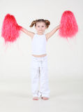 Little girl holds in raised hands pompoms Royalty Free Stock Photo