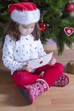 Little girl holds The Santa Letter Envelope. She is sitting beside Xmas Tree at home Royalty Free Stock Image