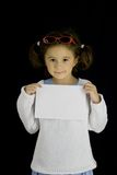 Little girl holds a sheet of white paper Royalty Free Stock Photography