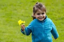 Little girl holds yellow flowers Royalty Free Stock Image