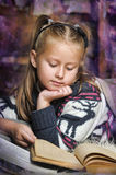 Little girl at home with a book Royalty Free Stock Image