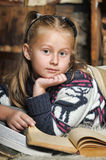 Little girl at home with a book Stock Photos