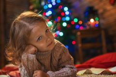 Little girl at home with a Christmas tree, presents and candles. Celebrating christmas Stock Images