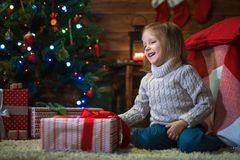 Girl at home with a Christmas tree, presents and candles celebra. Little girl at home with a Christmas tree, presents and candles celebrating christmas Royalty Free Stock Image