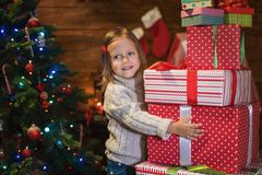 Girl at home with a Christmas tree, presents and candles celebra. Little girl at home with a Christmas tree, presents and candles celebrating christmas Royalty Free Stock Photos