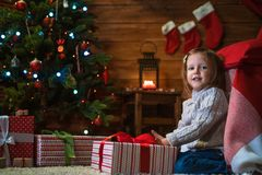 Girl at home with a Christmas tree, presents and candles celebra. Little girl at home with a Christmas tree, presents and candles celebrating christmas Stock Photos