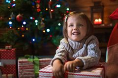Girl at home with a Christmas tree, presents and candles celebra. Little girl at home with a Christmas tree, presents and candles celebrating christmas Royalty Free Stock Photo