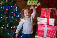 Girl at home with a Christmas tree, presents and candles celebra. Little girl at home with a Christmas tree, presents and candles celebrating christmas Stock Photography