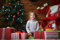 Girl at home with a Christmas tree, presents and candles celebra. Little girl at home with a Christmas tree, presents and candles celebrating christmas Stock Photo