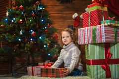 Little girl at home with a Christmas tree, presents and candles. Celebrating christmas Royalty Free Stock Photos