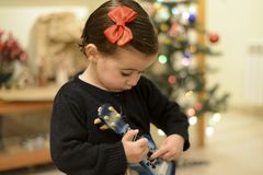 Little girl at home with decoration and defocused Christmas lights. Portrait of little girl with tie in hair at home with decoration and defocused Christmas stock photo