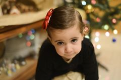 Little girl at home with decoration and defocused Christmas lights. Portrait of little girl with tie in hair at home with decoration and defocused Christmas royalty free stock photo