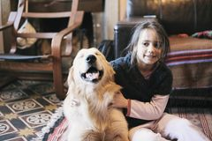 Little girl at home with her golden retriever dog. Have affectionate gestures Royalty Free Stock Images
