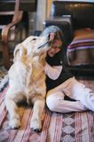 Little girl at home with her golden retriever dog. Have affectionate gestures Stock Photos