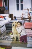 Little girl at home with her golden retriever dog have affection. Ate gestures Stock Images