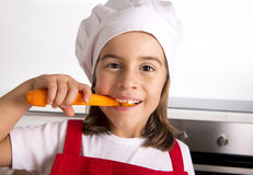 Little girl at home kitchen in red apron and cook hat holding carrot and biting happy Royalty Free Stock Images