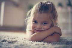 Little girl at home , lying on floor. stock images