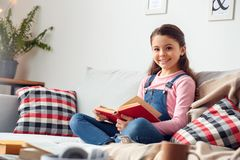 Little girl at home sitting holding book looking camera happy royalty free stock photo