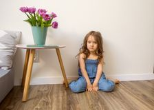 Little girl at home sitting near bed playing royalty free stock photos