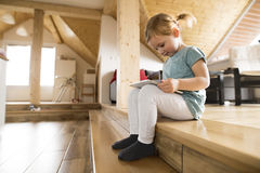 Little girl at home watching something on tablet. Stock Photos