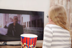 Little girl at home watching TV in 3d glasses. Eating popcorn Royalty Free Stock Images