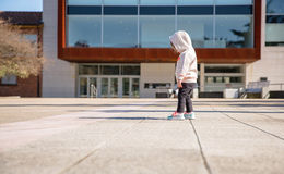 Little girl with hoodie looking her sneakers Royalty Free Stock Photography
