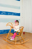 Little girl on a horse rocking chair Stock Image