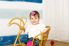 Little girl on a horse rocking chair Stock Images