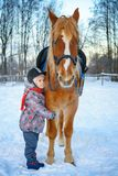 Little girl on a horse in winter, horseback riding stock photos