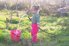 Little girl with hose in the garden Stock Photo