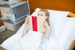 Little girl in hospital bed. Little girl lying in hospital bed and hiding face with book Royalty Free Stock Images