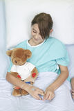 Little girl in hospital bed with teddy bear Stock Images