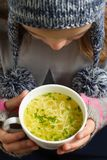 Little girl with hot soup in a bowl. Little girl with hot chicken soup  in a bowl in an cold day Stock Photo