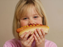 Little girl with hot dog smiling Royalty Free Stock Image