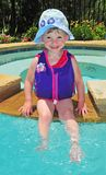 Little Girl in the Hot Tub. A young girl sits in a hot tub in a suburban backyard Royalty Free Stock Image