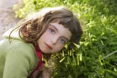 Little girl hug grass happy in green meadow Stock Images