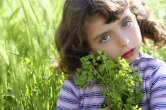 Little girl hug green plant meadow spikes Royalty Free Stock Photos