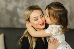 Little girl hug mother and smile. Happy young mom with her daughter at home stock photography