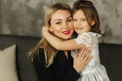 Little girl hug mother and smile. Happy young mom with her daughter at home stock photos