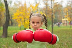 A little girl in huge boxing gloves makes an evil face Stock Photo