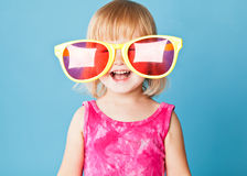 A little girl with a huge sunglasses. On blue background Royalty Free Stock Image