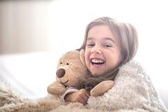 Little girl hugging bear toy on light background stock photo