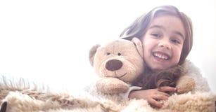 Little girl hugging bear toy on light background stock photography