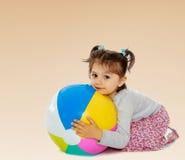 Little girl hugging a big ball Stock Image