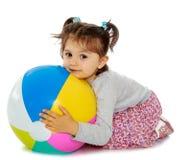 Little girl hugging a big ball Stock Photos