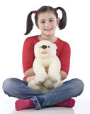 Little girl is hugging big teddy bear. On a white background royalty free stock photo