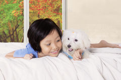 Little girl hugging canine in the bedroom Stock Image