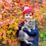 Little girl hugging a cat. In the garden in autumn Royalty Free Stock Images